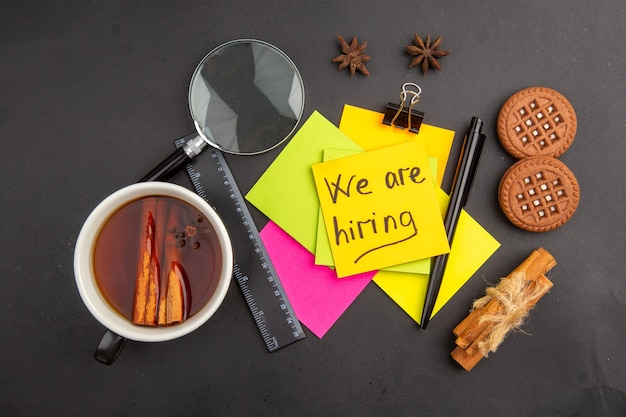 Top view we are hiring written on sticky note colorful sticky notes lupa pen cinnamon sticks ruler cup of tea flavored by cinnamon biscuits anises on dark