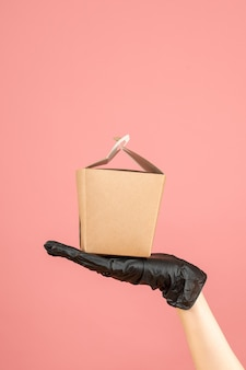 Top view of wearing black glove hand holding small box on pastel peach