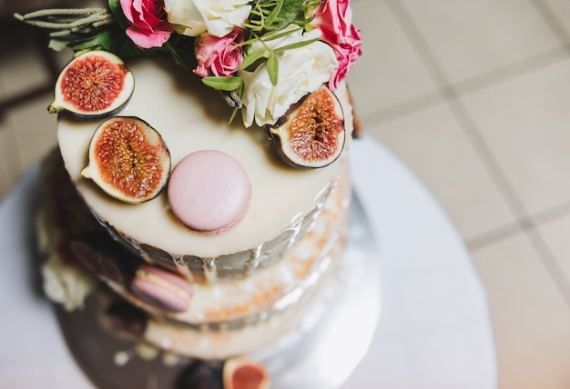 Top view of a wedding cake decorated with fig fruit, macarons and flowers