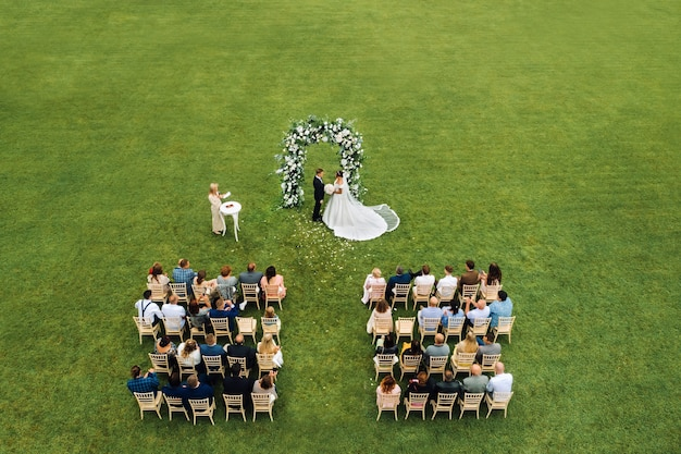 Top view of the wedding ceremony in a green field with guests sitting on chairs. wedding venue on the green lawn.