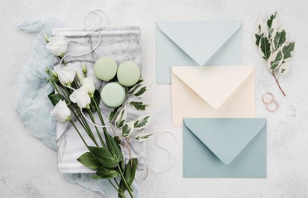 Вид сверху на свадебные пригласительные конверты с цветами