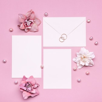 Top view wedding invitation with rings on the table