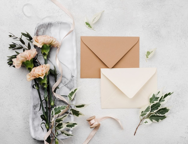 Top view wedding invitations with flowers on the table