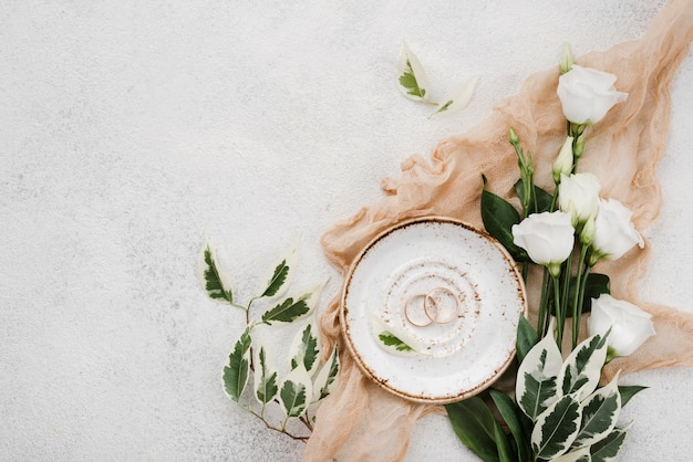 Top view wedding rings and flowers with copy space