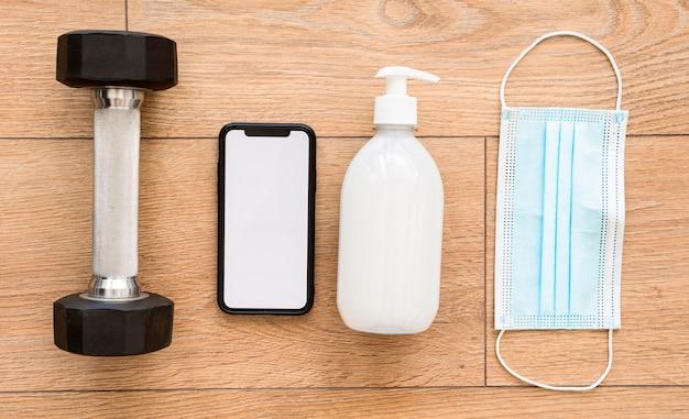 Vista dall'alto del peso con smartphone e disinfettante per le mani