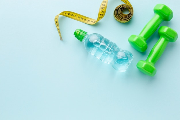 Top view weights and bottle of water with copy space