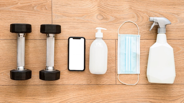 Top view of weights with cleaning solution and smartphone for gym