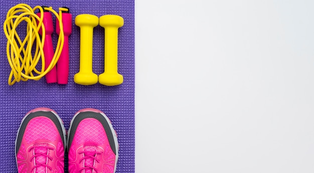 Top view of weights with jump rope and sneakers