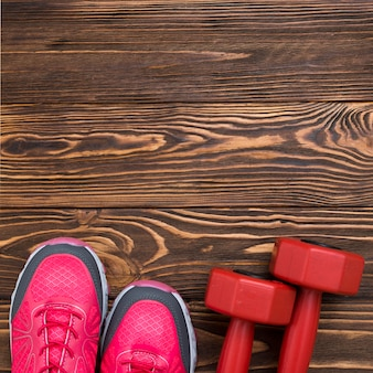 Top view of weights with sneakers on wooden background