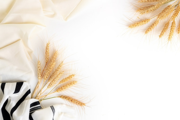 Top view. wheat ears and tallit on white background