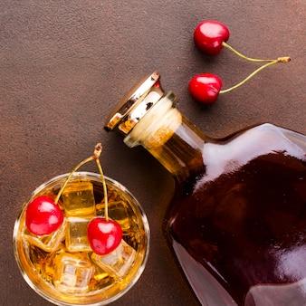 Vista dall'alto bicchiere di whisky e ciliegie con bottiglia
