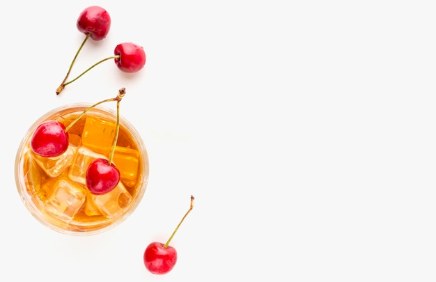 Top view whiskey glass and cherries with copy-space