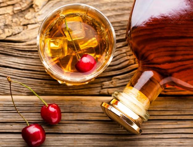 Vista dall'alto bicchiere di whisky con ghiaccio e ciliegie e bottiglia
