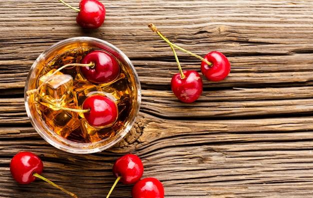 Vista dall'alto bicchiere di whisky con ghiaccio e ciliegie