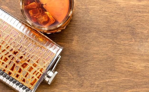 Whisky con vista dall'alto sulle rocce e boccetta con copia-spazio