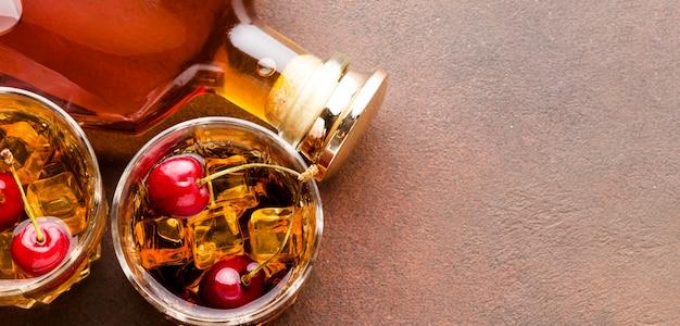 Whisky con vista dall'alto sulle rocce con ciliegie e bottiglia con copia-spazio