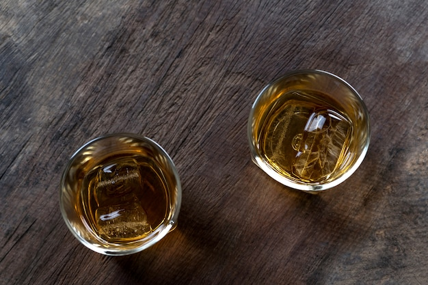 Top view of whiskey with ice in glass on wooden table
