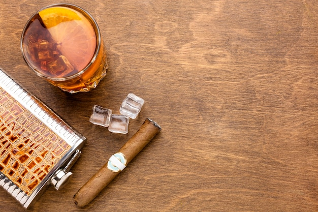 Top view whiskey with orange and cigar with copy space