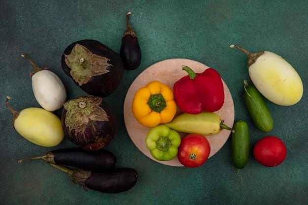 上面図白と黒のナス、スタンドにピーマントマト、緑の背景にきゅうり