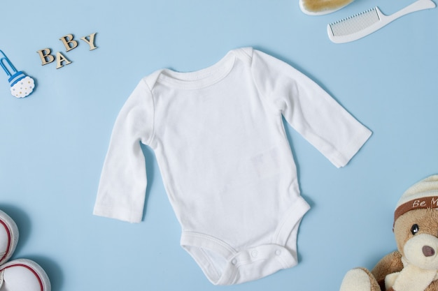 Top view white baby bodysuit on a blue surface