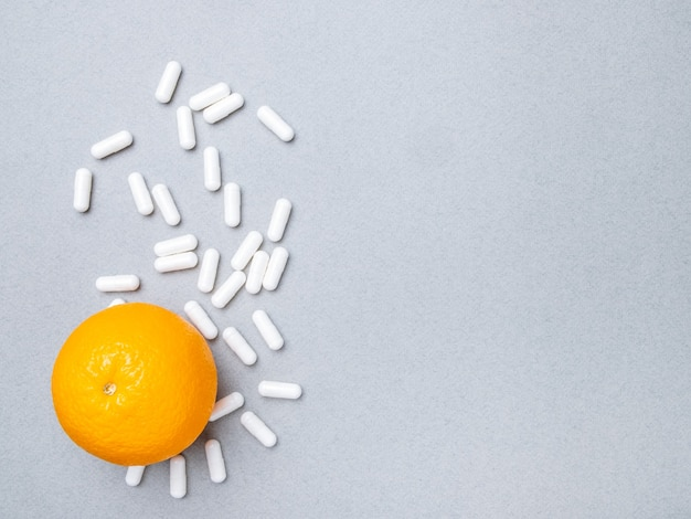 Top view on white big oval pills and ripe orange on a gray background