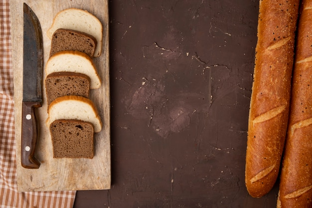 Top view of white and black bread slices and knife on cutting board with baguettes on maroon background with copy space