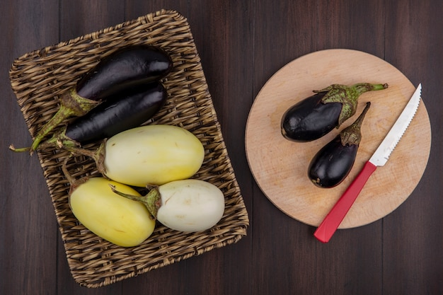 Top view white and black eggplant on a stand and on a cutting board with a knife  on a wooden background