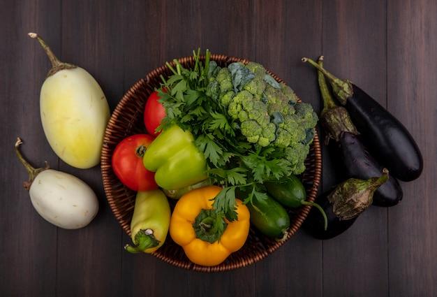 Vista dall'alto melanzane bianche e nere con broccoli peperoni cetrioli e pomodori nel cestino su fondo di legno