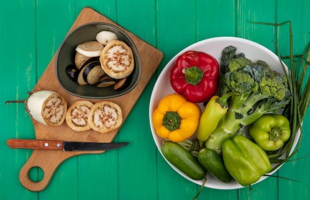 Vista dall'alto melanzane a fette bianche e nere con un coltello su un tagliere con broccoli, cetrioli, cipolle verdi e peperoni in un piatto su uno sfondo verde