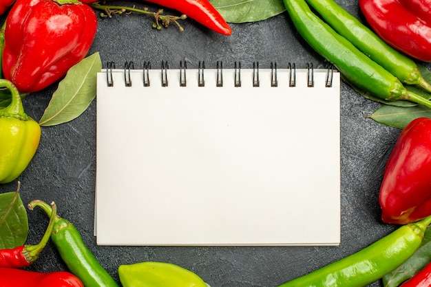 Top view white blank notebook with autumn vegetables on gray surface with free space