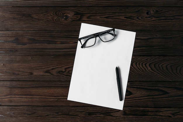 Top view of a white blank sheet of paper with a pen and glasses on a wooden table.