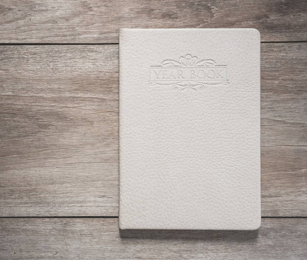 Top view of white book on old wooden plank background