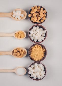 Vista dall'alto zucchero bianco e marrone in ciotole con cucchiai