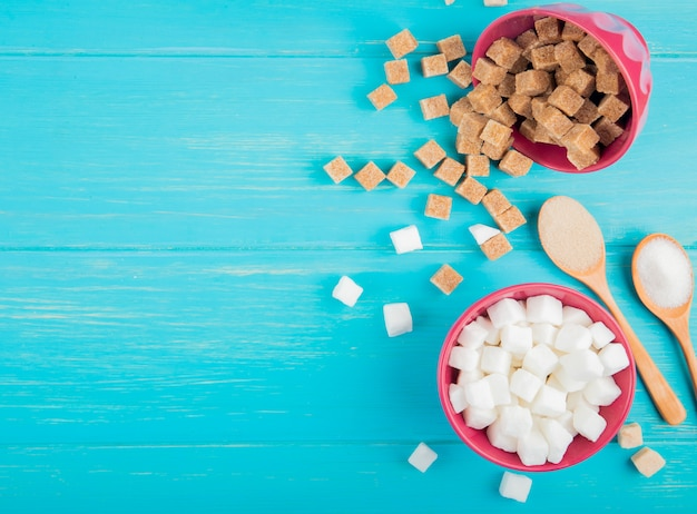 Top view of white and brown sugar cubes in bowls on blue wooden background with copy space