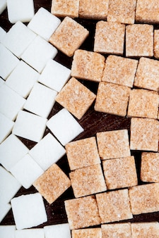 Top view of white and brown sugar cubes scattered on dark wooden background