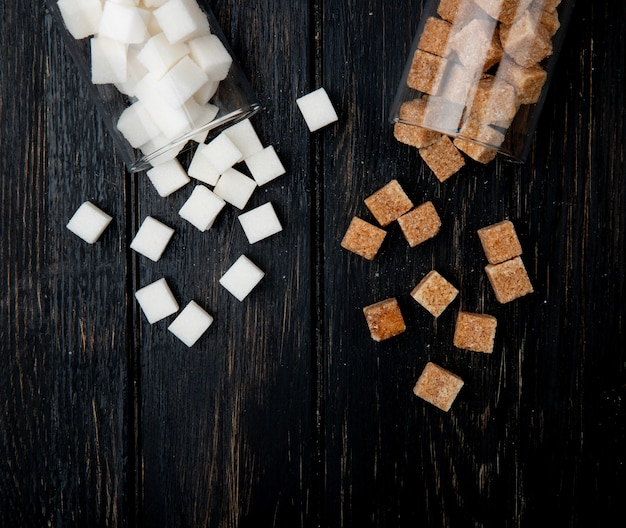 Top view of white and brown sugar cubes scattered from glass jars on dark wooden background