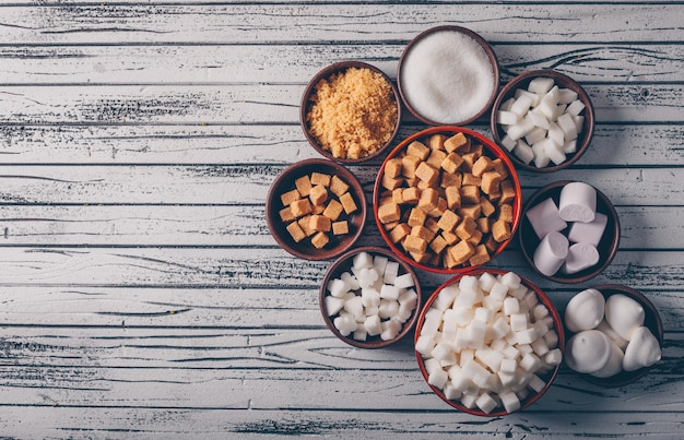 Top view white and brown sugar with marshmallow in bowls on light wooden table.