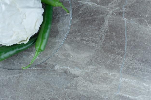 Vista dall'alto del cavolo bianco al centro dei peperoncini verdi.