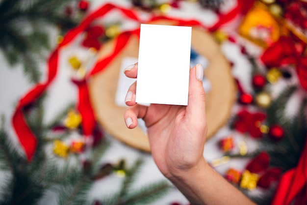 Top view of white card, mockup in female hand on festive  background