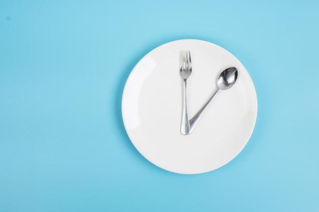 파란색 배경에 나이프, 숟가락, 포크가 있는 위쪽 보기 흰색 세라믹 접시. 간헐적 단식, 케토제닉 다이어트, 체중 감량, 식사 계획 및 건강 식품 개념