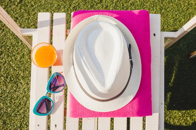 Top view of white chair with towel, hat and sunglasses