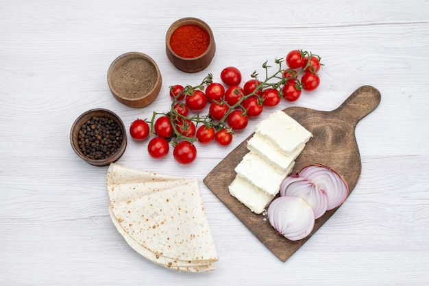 トップビューホワイトチーズと新鮮な赤いトマト玉ねぎ、白い机の野菜料理の食事ランチ