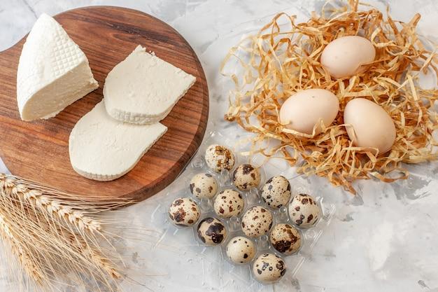 도마 위의 흰색 치즈 조각 짚으로 만든 밀 스파이크에 있는 닭고기 달걀 테이블에 메추라기 알