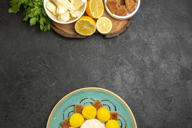 暗い表面の食事フルーツミルク食品にケーキキャンディーとレモンスライスを添えた上面図ホワイトチーズ