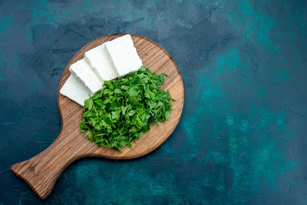Top view of white cheese with fresh greens on dark blue surface