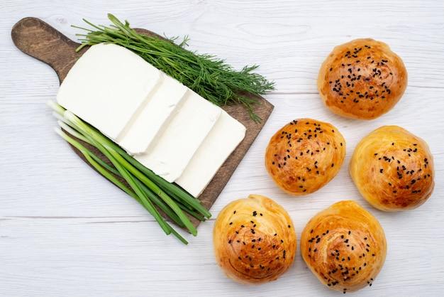 Вид сверху белый сыр с зеленью и булочками на белом столе, хлеб, еда, завтрак