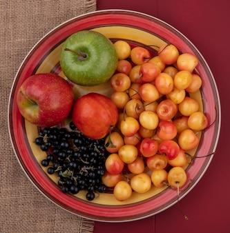 Вид сверху белая вишня с черной смородиной, персиком и цветными яблоками на тарелке на красном столе