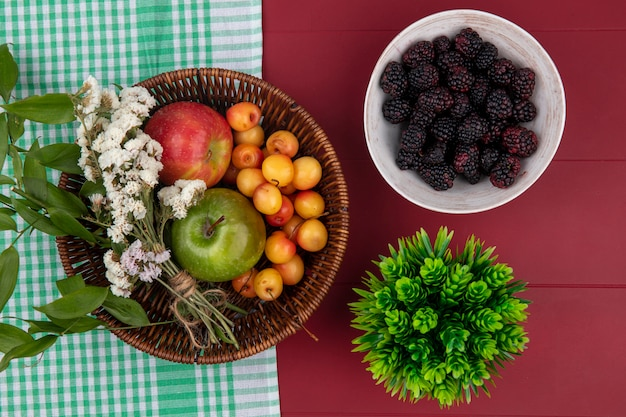 Top view white cherry with colored apples and flowers in a basket and blackberries in a bowl on a red table
