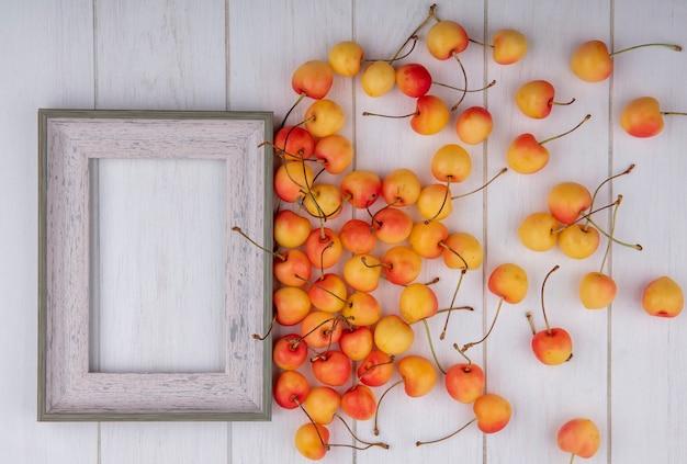 Vista dall'alto della ciliegia bianca con una cornice grigia su una superficie bianca