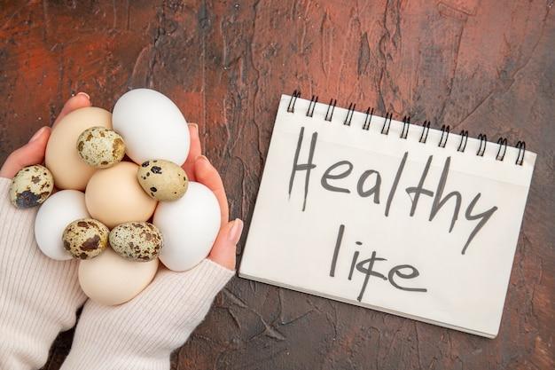暗いテーブルの上の女性の手で白い鶏卵の上面図